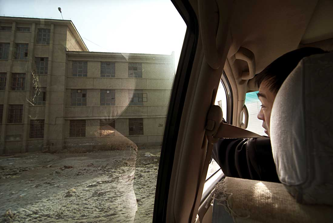 Mr Jia in his oil company LandCruiser in January 2010, looking out at the bingtuan high school that he graduated from in the early 1980s.